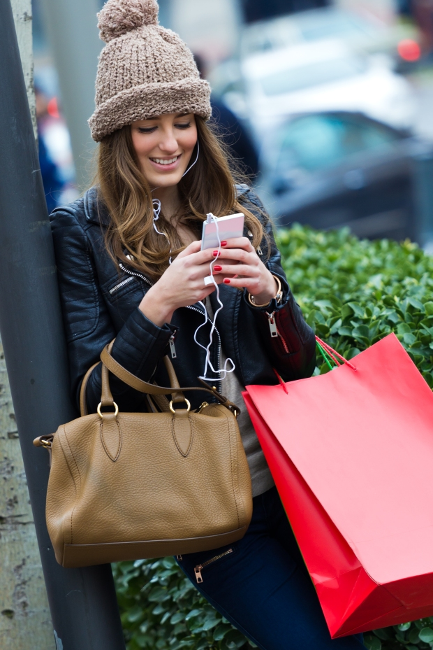 Young woman shopping in the city with his mobile phone