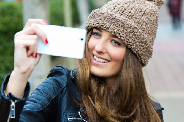 Cute brunette woman taking photo of herself on the street