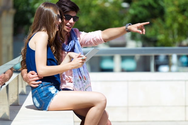 Happy young couple browsing internet with digital tablet  in the