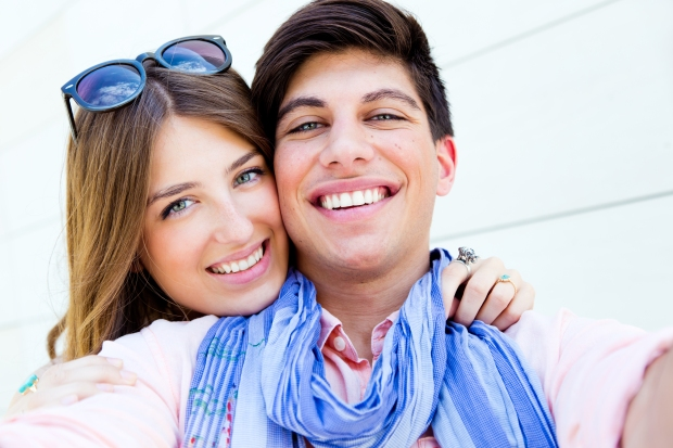 Outdoor portrait of happy young couple taking photos with a smar